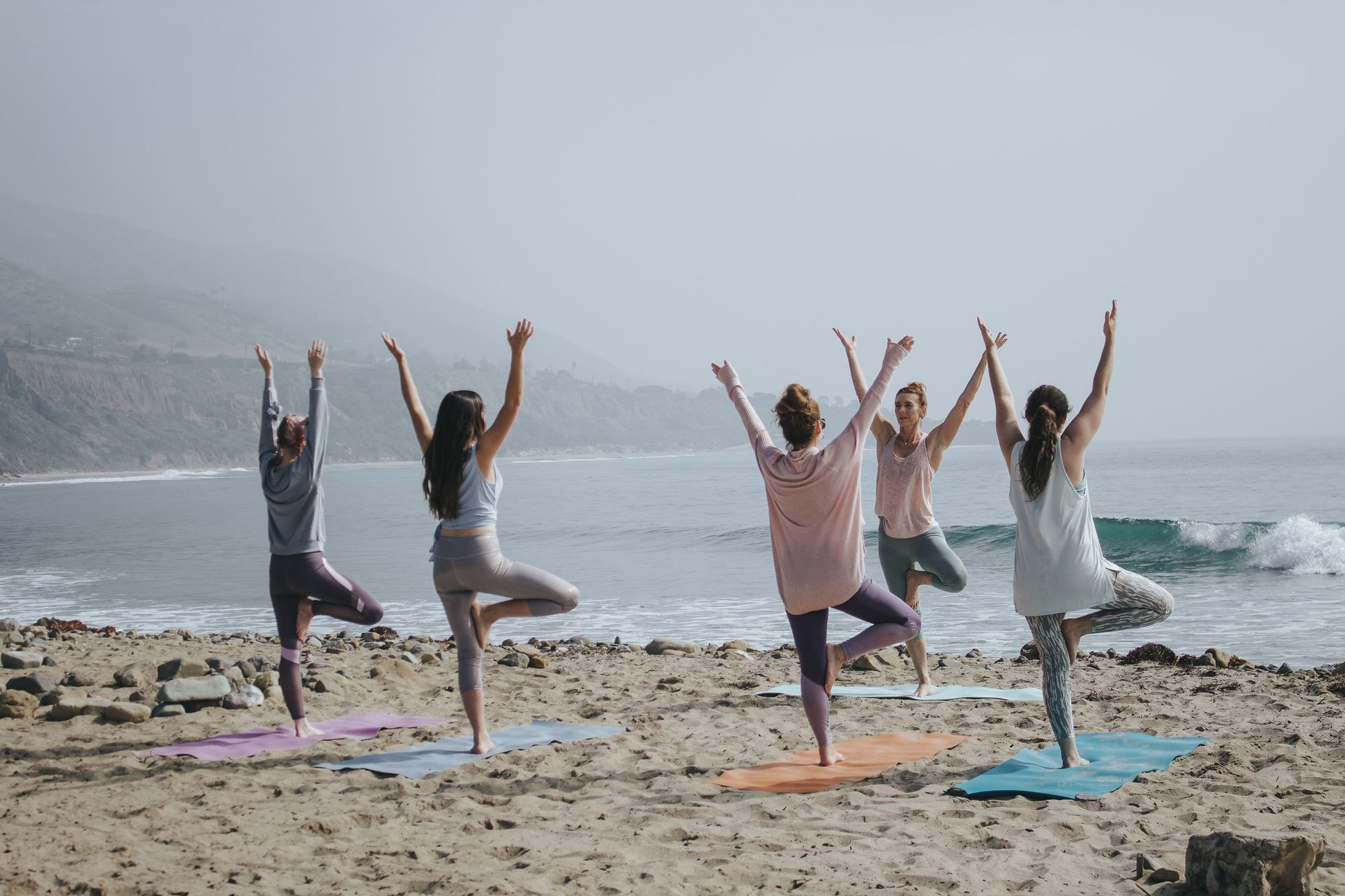 Practicing how to teach yoga with a small group of yoga students at the beach