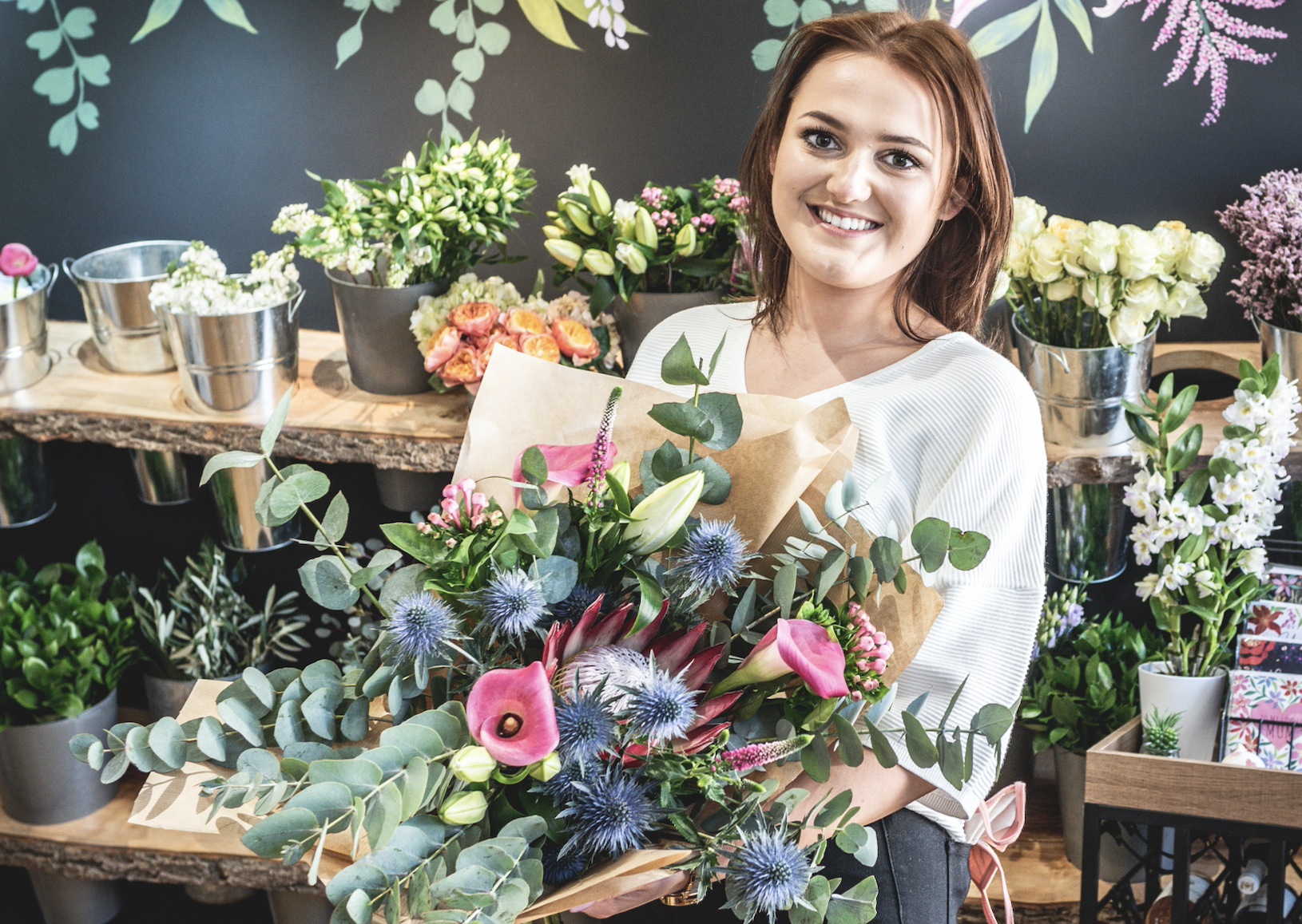 A young woman, Shannon, is holding a colourful bouquet she designed